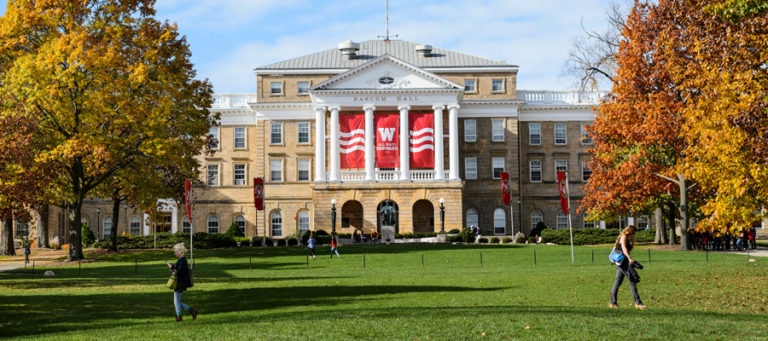 Bascom Hill in fall with students walking in the grass.