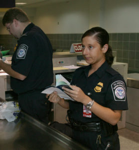 A Customs and Border Patrol agent inspects a traveler's passport.