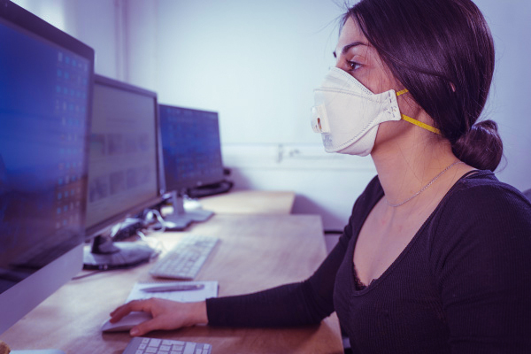 Female student wearing a mask uses computer in computer lab