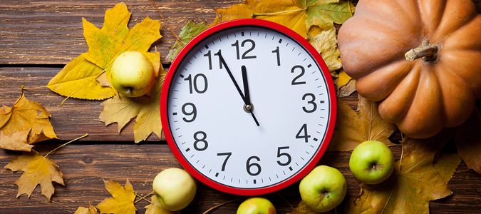 Red clock on a table with fall colored leaves, apples, and a pumpkin.