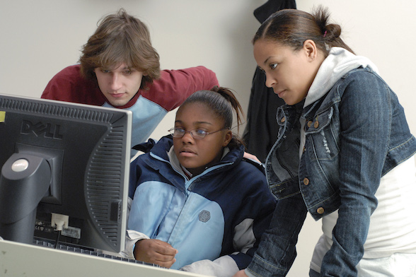 3 high school students from diverse backgounds gathered around a computer display