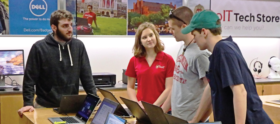 Students consulting with Tech Store employee