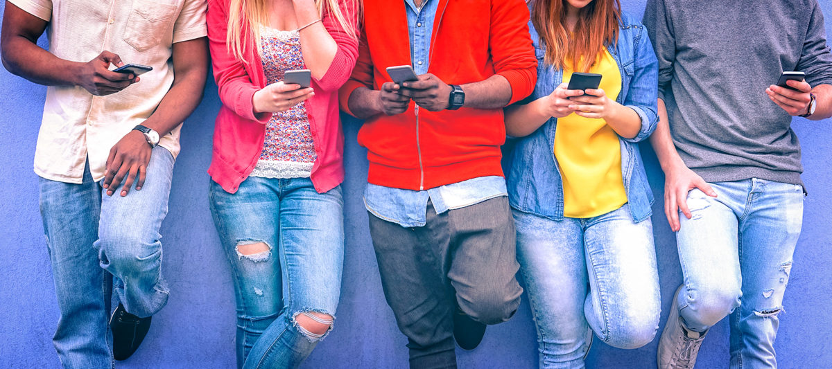 A group of teens standing against a wall using their phones.
