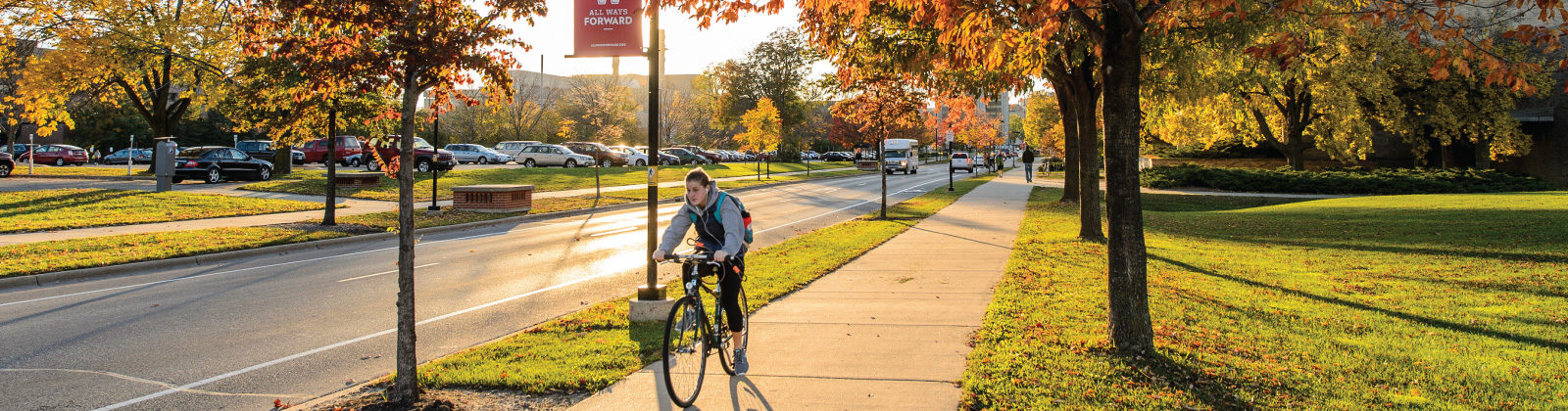 Student riding bicycle on UW-Madison campus during fall season