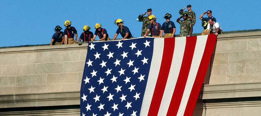 Firefighters and soldiers unfurl flag