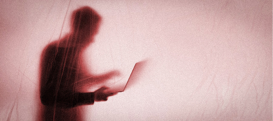 Shadowy figure with laptop